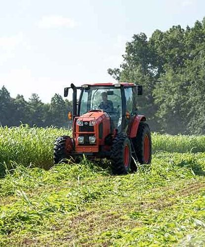 Farmer driving a tractor over his crops